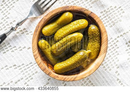 Small pickles. Marinated pickled cucumbers in wooden bowl on white table. Top view.