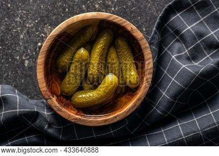 Small pickles. Marinated pickled cucumbers in wooden bowl on black table. Top view.