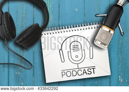 Top View Of Headphones, Microphone And Note Pad With Podcast Logo On Rustic Wooden Table