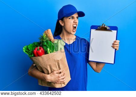 Young hispanic woman wearing courier uniform with groceries from supermarket and clipboard angry and mad screaming frustrated and furious, shouting with anger. rage and aggressive concept.