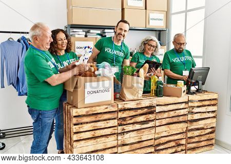Group of middle age volunteers smiling happy working at charity center.