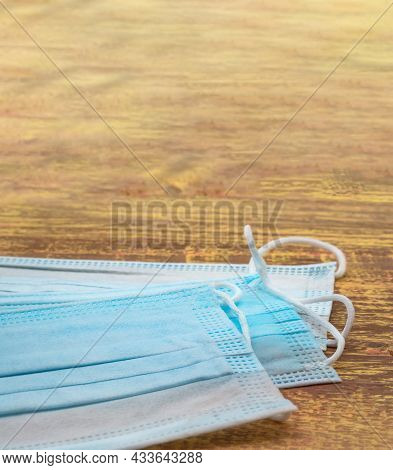 Disposable Surgical Mask. Stack Of Surgical Masks On Wooden Table. Blue Medical Mask. Medical Protec