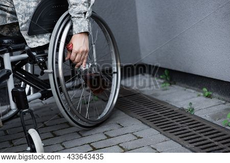 Partial View Of Handicapped Military Man With Bottle Of Whiskey Sitting In Wheelchair Outdoors