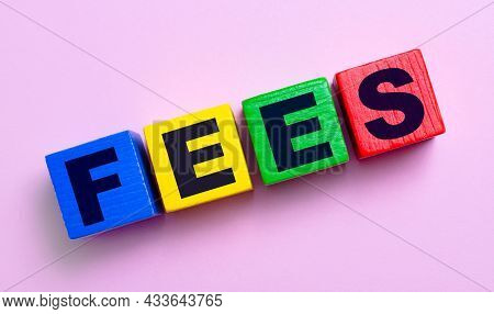 On A Light Pink Background, Multi-colored Wooden Cubes With The Text Fees