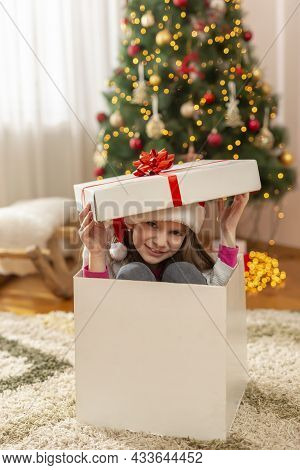 Beautiful Little Girl Wearing Santa Hat Having Fun While Playing At Home On Christmas Day, Hiding In