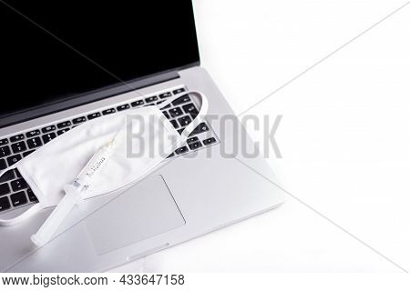 Face Mask And Syringe With Antivirus On The Computer Keyboard