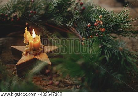 Stylish Christmas Wreath With Rustic Burning Candle On Old Wooden Background. Christmas Advent. Merr