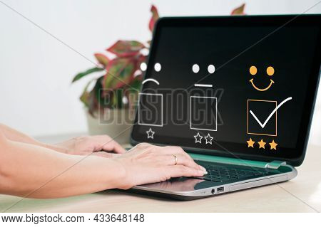On A Laptop Computer, A Woman Selects A Facial Smiling Emoticon To Display On The Virtual Screen. Th