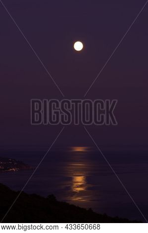 Full Moon Sea. The Supermoon Is Orange In A Purple Sky Over The Ocean. Vertical Natural Night Backgr
