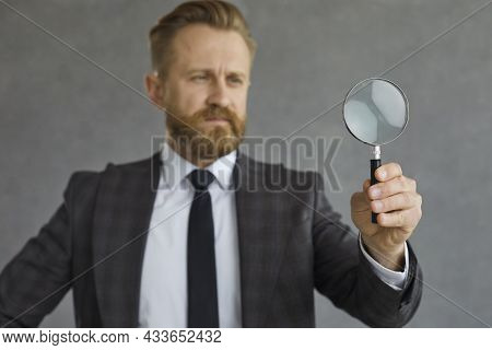 Serious Businessman Searching For Something And Looking Through A Magnifying Glass
