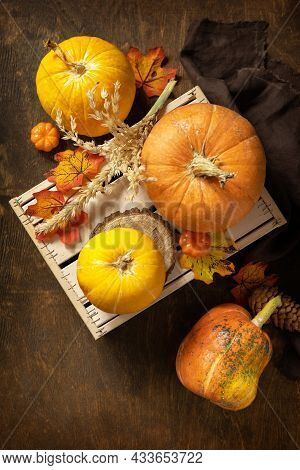 Festive Autumn Seasonal Decorations With Pumpkins And Leaves On A Rustic Wooden Background. Concept