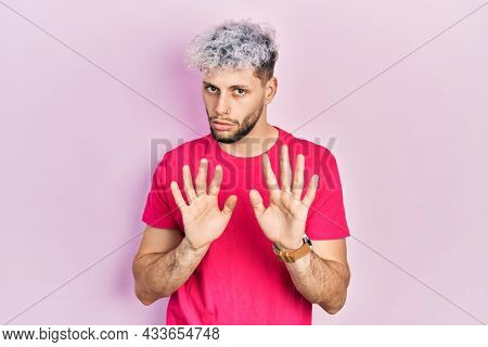 Young hispanic man with modern dyed hair wearing casual pink t shirt moving away hands palms showing refusal and denial with afraid and disgusting expression. stop and forbidden.