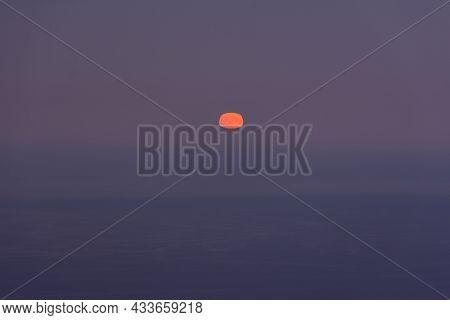 Full Moon Sea. The Supermoon Is Orange In A Purple Sky Over The Ocean. Horizontal Minimalistic Natur