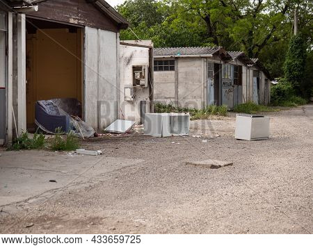 Parma, Italy - May 2021:dilapidated Little Houses Among The Trees And Vegetation And Dump Of Old App