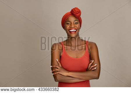 Portrait of beautiful middle aged woman with crossed arms and red headband smiling against brown wall. Cheerful woman wearing ethnic headscarf with folded arms while looking at camera.