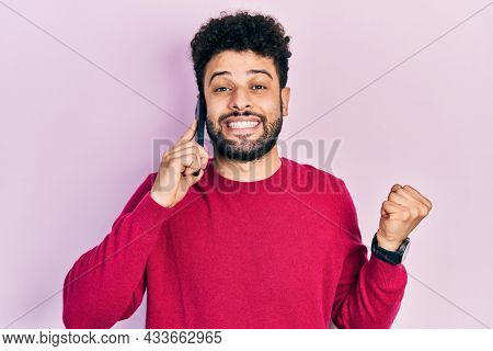 Young arab man with beard having conversation talking on the smartphone screaming proud, celebrating victory and success very excited with raised arm