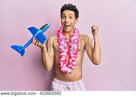 Young handsome man wearing swimsuit and hawaiian lei holding airplane toy screaming proud, celebrating victory and success very excited with raised arms