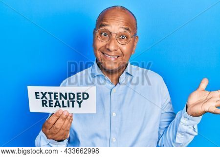 Middle age latin man holding paper with extended reality message celebrating achievement with happy smile and winner expression with raised hand