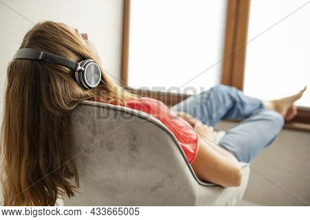 Young Beautiful Woman Sitting In Armchair Near A Window And Listening To Music Using Headphones. Hap