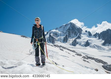 Happy Cheerful Sincerely Laughing Young Female Portrait In Climbing Harness, Crampons, Sunglasses, M