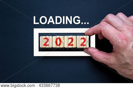 2022 Happy New Year Symbol. Wooden Cubes Symbolize The Change To The New Year 2022. Businessman Hand