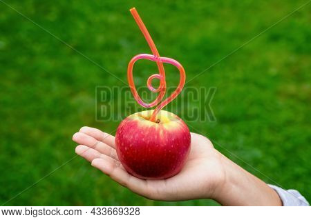 Close-up Of Red Apple In Shape Of Heart With Tube Sticking Out Of It On Woman Hand On Background Of