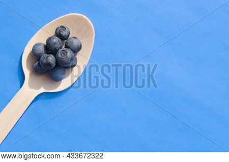Flat Lay Of Recycled Spoon And Juicy Fresh Blueberries On Color Table. Space For Text. Isolated Ripe