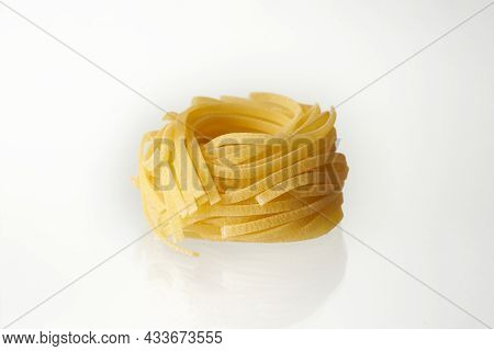 Raw Rolled Tagliatelle Pasta Isolated On White Background