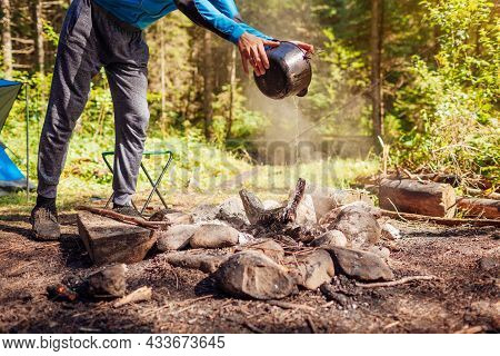 Man Extinguishing Campfire With Water From Cauldron In Summer Forest. Put Out Campfire By Tent. Trav