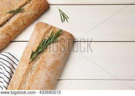 Delicious Ciabattas With Rosemary On Beige Wooden Table, Flat Lay. Space For Text