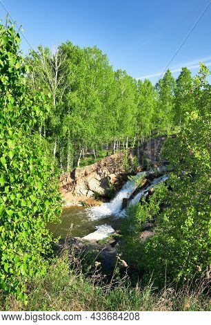 Forest Waterfall Among Birches In Spring. Young Birches With Fresh Spring Foliage, A Waterfall Far B