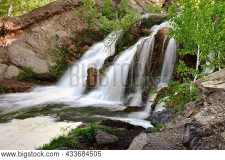 Belovsky Waterfall In The Spring. A Small Waterfall Among The Rocks, Surrounded By Birch Trees With