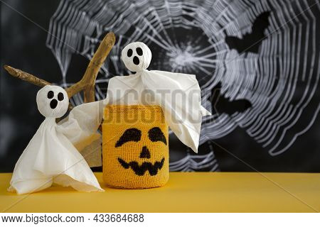 Two Ghosts, Candlestick With Scary Halloween Grimace On Background Of Cobweb. Halloween Concept