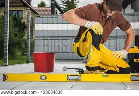 Caucasian Worker In His 40s Finishing Patio Bricks Pavement. Checking Levels With Spirit Level Tool.