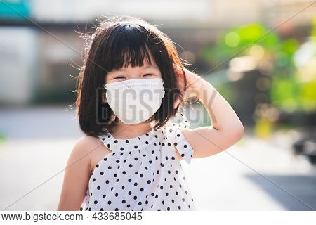 A 4-5 Year Old Girl Wears Face Mask. Sweet Smiling Child Take Walk In The Morning. Sunlight Hits The