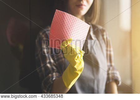 Young Female Hands In Yellow Rubber Gloves Hold A New Pink Sponge For Cleaning The House And Wiping