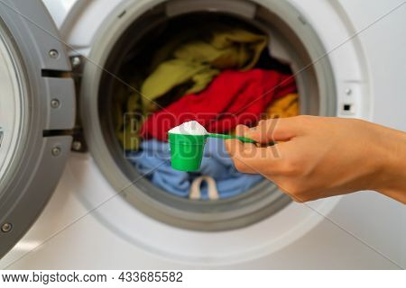 A Womans Hand Holds A Cap With Washing Powder Against The Background Of A Washing Machine With Brigh