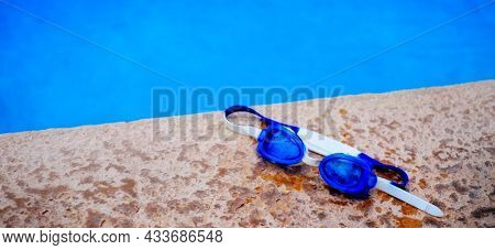 Detail of blue swim goggles for summer next to cool refreshing swimming pool