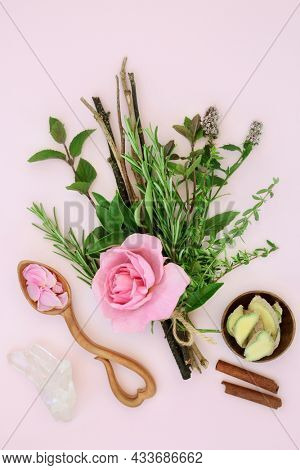 Ingredients for magical love potion with herbs and rose flower tied in a witches bundle with ginger and cinnamon spice, quartz crystal and love spoon with petals on pink. Romantic magic spell concept.