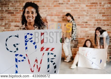 Multiracial young feminist women smiling while showing their placards indoors