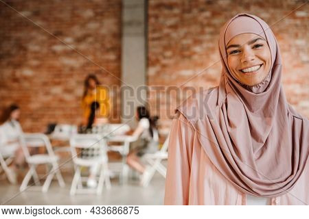 Close up of a happy mid aged islamic woman standing looking at camera with group of multiethnic women sitting at the table indoors during seminar only for women, feminism concept