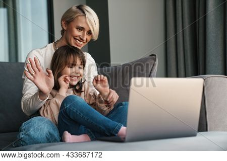 Happy young mother and her little daughter sitting on a couch with laptop computer, looking at screen, on a video call or watching movies, waving hand