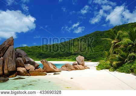 Anse Cocos beach with big granite stones in La Digue Island, Indian Ocean, Seychelles. Tropical landscape with sunny sky. Exotic travel destination.