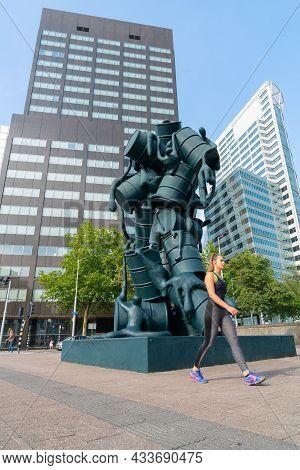 Rotterdam Netherlands - August 23 2017; Blurred Image Of Sporting Woman Walking Briskly Past Sculptu