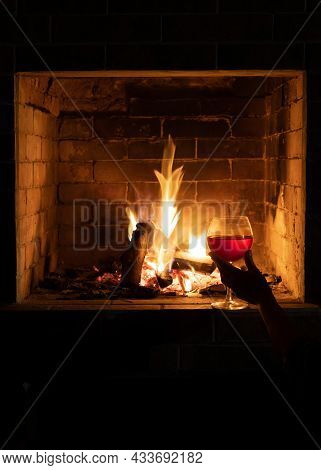 Female Hand With A Glass Of Red Wine In Front Of The Fireplace. The Fire In The Fireplace Burns Brig