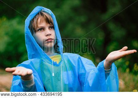Young Boy Tourist Hiker In Blue Raincoat Enjoying Warm Summer Rain