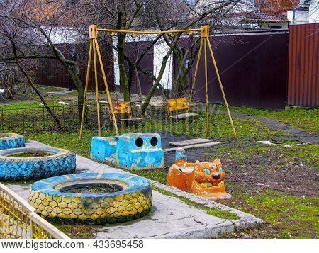 An Empty Playground With No Children. Old, Abandoned Playground With Swing. Consequences Of The Covi