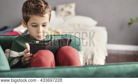 Cheerful Little Boy Smiling While Sitting On Couch And Using Tablet At Home. Modern Kid And Educatio