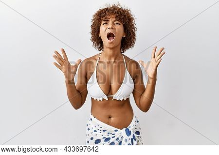 Young african american woman with curly hair wearing bikini crazy and mad shouting and yelling with aggressive expression and arms raised. frustration concept.