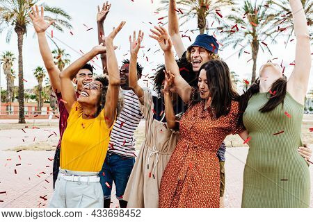 Happy Friends Throwing Confetti And Enjoying Summer Party Outdoors - Multiethnic Group Of Young Peop
